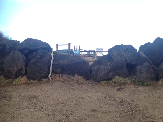 Walk through the boulders and through the metal fence